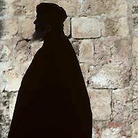 Israel, Jerusalem, Silhouette of Greek Orthodox priest outside Church of Holy Sepulcher on Palm Sunday