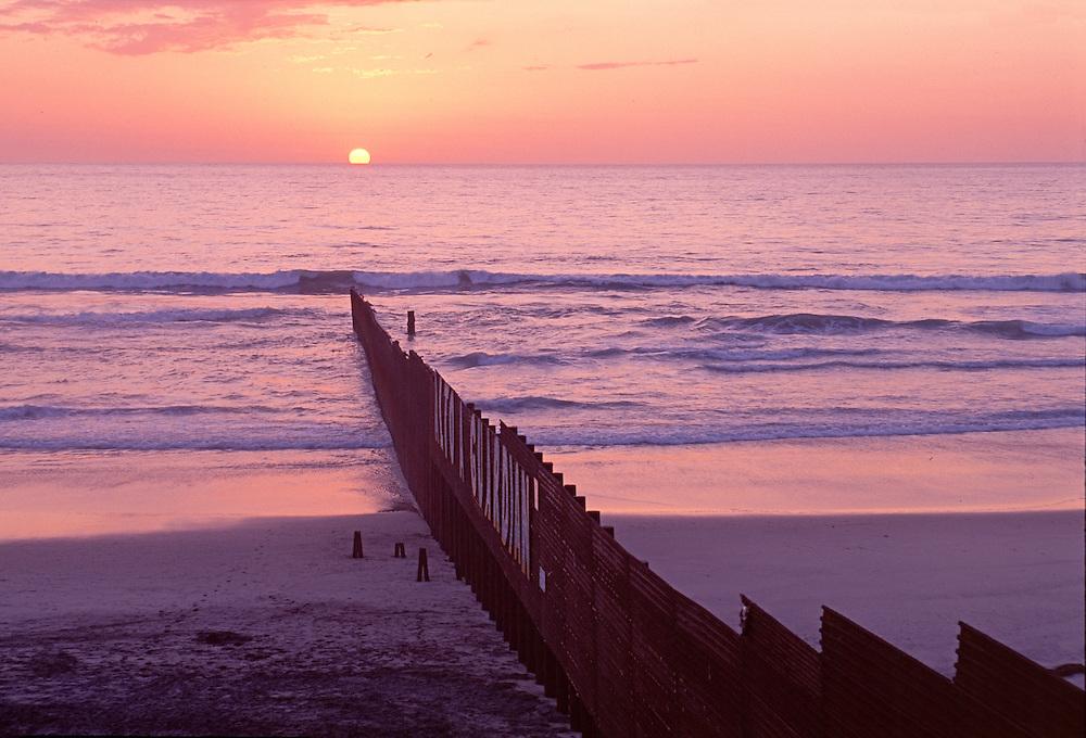 Sunset, Border Wall, USA-Mexico, Baja California. Pacific Ocean