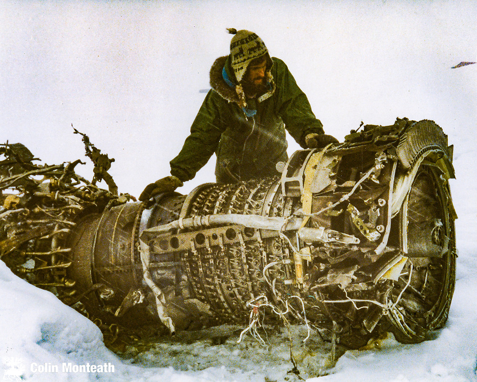 Colin Monteath with Air NZ DC-10 engine, crash site above Lewis Bay, Ross Island during recovery operation, December 1979
