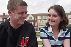 Homeless teenage boy and girl sitting on park bench talking,