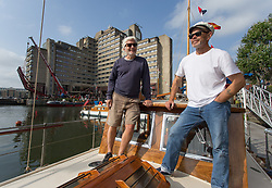 © Licensed to London News Pictures.  03/09/2021. London, UK. Jonathan Hooper (L) and Capitan Peter Brown pose for a photo on the boat called Hopalong at St Katharine Docks Marina on the River Thames ahead of the Classic Boat Festival this weekend. With 40 vintage sail and motor yachts, the Classic Boat Festival is part of Totally Thames' 25th festival. Photo credit: Marcin Nowak/LNP