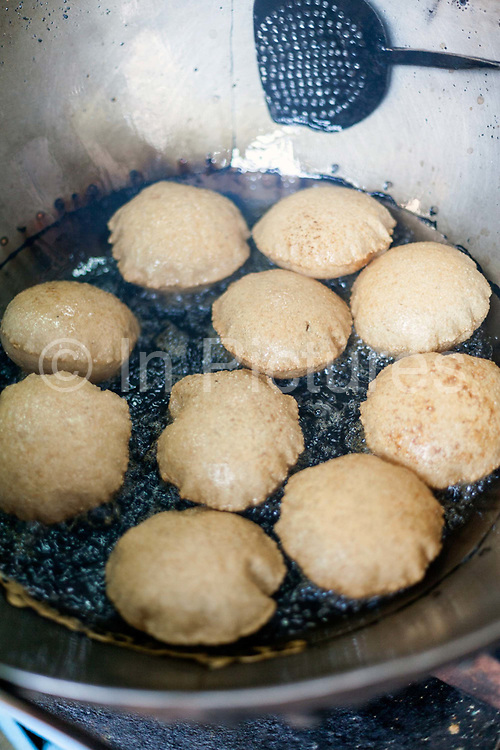 Nagori (small puris) frying in oil at Ram Swarup, a shop which has been  serving up breakfasts in the old city for over 70 years Old Delhi, India