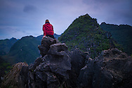 Lone woman in a red jacket sits atop Dong Van Karstic Plateau in Ha Giang Province, Vietnam, Southeast Asia