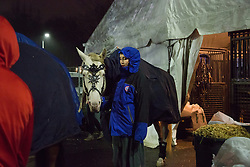 """Members of The Thundering Cossack Warriors bring their horses to the arena in the rain. Ringling Bros. and Barnum & Bailey Circus started in 1919 when the circus created by James Anthony Bailey and P. T. Barnum merged with the Ringling Brothers Circus. Currently, the circus maintains two circus train-based shows, the Blue Tour and the Red Tour, as well as the truck-based Gold Tour. Each train is a mile long with roughly 60 cars: 40 passenger cars and 20 freight. Each train presents a different """"edition"""" of the show, using a numbering scheme that dates back to circus origins in 1871 — the first year of P.T. Barnum's show."""