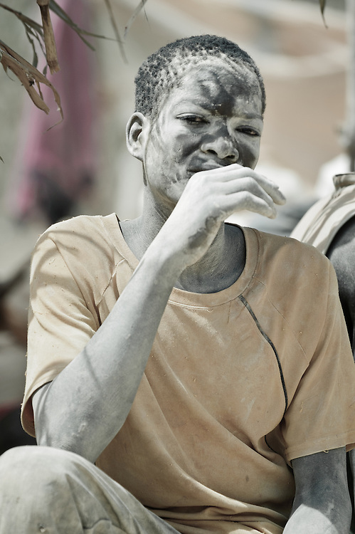 Stock photograph of a young African gold miner in Burkina Faso, exhausted and covered in mud from a day down the shaft digging for ore.