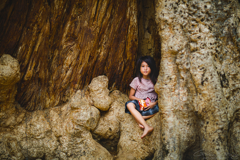 A girl eating snacks whilst sitting on a root of a large tree, Ta Phrom Temple, Siem Reap, Cambodia