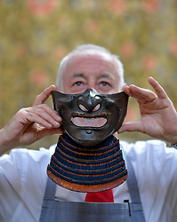 Pictured: Pictured: Bonham's Danny McIlwraith with a 19th century Samurai 'menpo' half mask piece of armour from Japan, expected to fetch £250 - £350 GBP.<br /> <br /> Rare Asian art was on show for a photocall before it goes up for sale at Bonham's in Edinburgh.<br /> <br /> © Dave Johnston / EEm