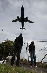 "© Licensed to London News Pictures. 27/10/2016. London, UK. A man and his son stand on the flight path as an airliner comes into land at Heathrow Airport. The government has announced that a third runway will be built at the United Kingdom's busiest airport. The Cabinet are divided - with Foreign Secretary Boris Johnson saying that the project is ""undeliverable"". Conservative MP for Richmond Zac Goldsmith has resigned. Photo credit: Peter Macdiarmid/LNP"
