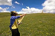A Tibetan man reads a prayer flag on a mountain top near Litang, Tibet.