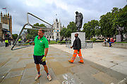 """Workers are seen mounting barriers around Parliament Square and Winston Churchill Monument after a protest """"for Afghanistan"""" is announced to be held outside Westminster Palace, Houses of Parliament in central London on Wednesday, Aug 18, 2021. Some Western political and human rights groups have expressed a variety of outrage following the military departure of the United States and its armed allies from Afghanistan. British Prime Minister Boris Johnson is expected to address the Parliament later today. (VX Photo/ Vudi Xhymshiti)"""