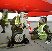 Engineering ground staff of the Red Arrows, Britain's RAF aerobatic team, makes repairs to a BAE Systems Hawk nosewheel. Wearing ear-defenders, military green overalls and fluorescent tabard, a 'line' engineer from the elite 'Red Arrows', Britain's prestigious Royal Air Force aerobatic team, inspect the nosewheel assembly of a Hawk aircraft immediately after a winter training flight at the team's headquarters at a damp RAF Scampton, Lincolnshire. The man is a member of the team's support ground crew (called the Blues because of their distinctive blue overalls worn at summer air shows). The team's support ground crew who outnumber the pilots 8:1 and without them, the Red Arrows couldn't fly. Eleven trades are imported from some sixty that the RAF employs and teaches.