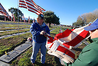 In the early morning chill on Veteran's Day, Janet Wolhogemuth and Armando Dimas raise one of hundreds of American flags at Garden of Memories in Salinas.