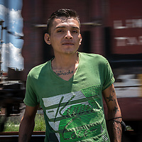 José is from Honduras, he is travelling through Mexico to the US. Here is stands in front of a fast-moving freight train that he has been travelling on. In four weeks travel from Honduras, much of it on foot and on the dangerous freight rail network known as La Bestia he had experienced violence from Mexican migration police and had had to walk for days without eating.