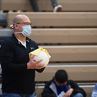 Jovito Sabal, a parent volunteer for Rehoboth Christian cleans a volleyball between plays at the Rehoboth Christian and Ramah varsity volleyball game Tuesday in Rehoboth. The volleyballs were sanitized throughout the game as a COVID-19 precaution.
