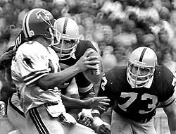 Atlanta quarterback Steve Bartkowski rushed by John Matuszak and Dave Browning. (1979 photo by Ron Riesterer)