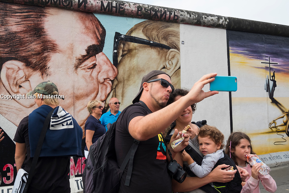 Tourists taking selfie photograph of mural painted on original section of Berlin Wall at East Side gallery in Berlin, Germany ...Editorial Use Only