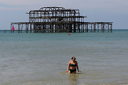 © Licensed to London News Pictures. 30/05/2021. Brighton, UK. A woman swimming in the sea on the hottest day of the year so far. According to the Met Office, a high of 24 degrees celsius is forecast for the bank holiday weekend, after weeks of rain in the South East of England. Photo credit: Dinendra Haria/LNP