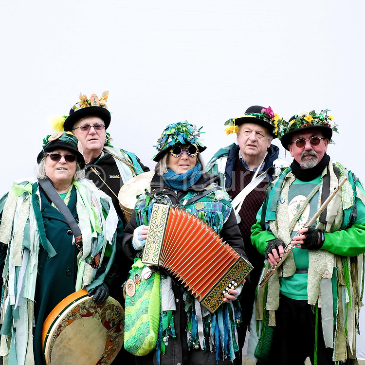 Portrait of the Makara Morris musicians wearing traditional costume at an orchard-visiting wassail at Sledmere House in the Yorkshire Wolds, United Kingdom on 20th January 2018. Wassail is a traditional Pagan winter celebration in cider-producing regions of England, reciting incantations and singing to the trees to promote a good harvest for the coming year. Pieces of toast soaked in cider are hung in the branches to attract robins to the tree as these are said to be the good spirits of the orchard. To ward off evil spirits, villagers scare them away by banging pots and pans and making as much noise as possible