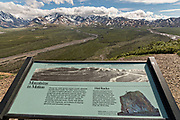 View of the Polychrome Hills and the Alaska Range and the Toklat River guided by a visitor sign in Denali National Park Alaska. Denali National Park and Preserve encompasses 6 million acres of Alaska's interior wilderness.