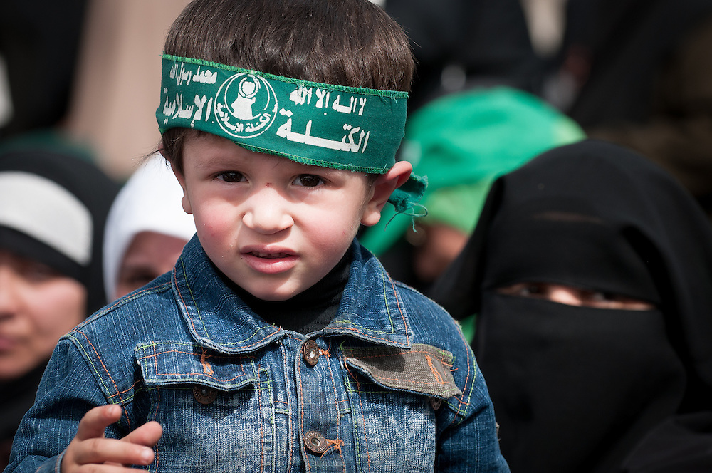 A boy sits in his mother's lap, wearing a Hamas headband.