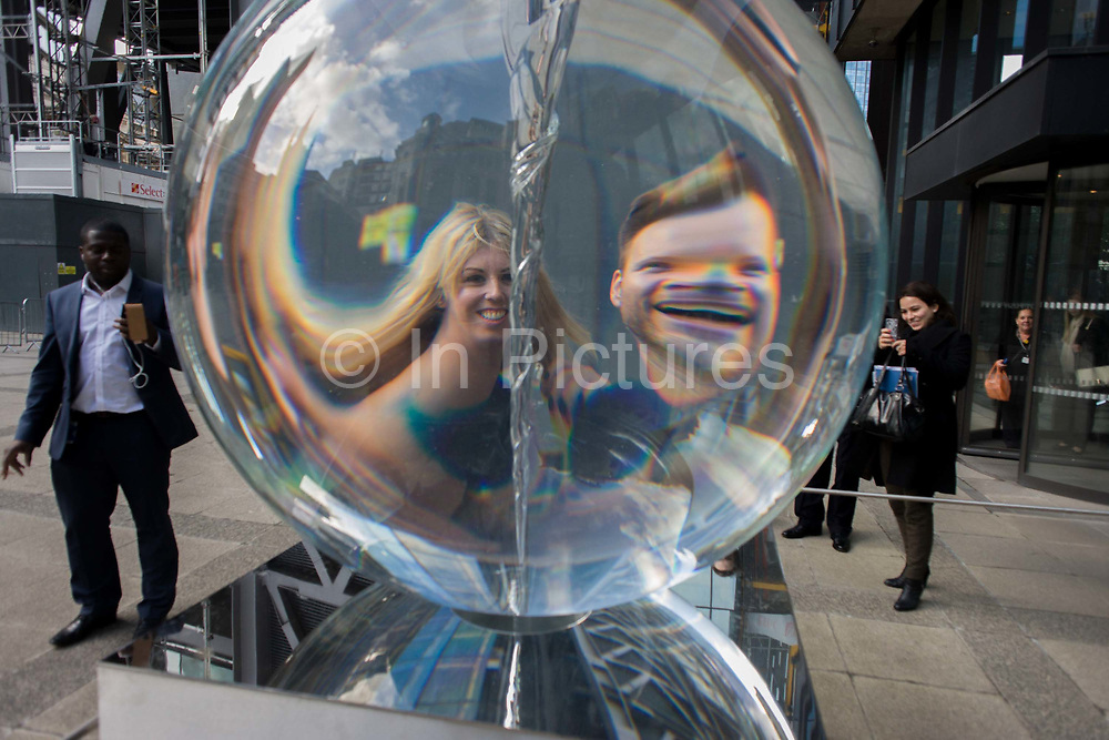 Distorted faces of a couple seen through Petroc Sesti's art instillation called Time Fold in Great Helen's Square, in the City of London. Passers-by stop to take pictures with their smartphones as the magnified heads of others are seen through the giant prism's optics. Petroc Sesti is a London based British artist and Time Fold bends light like a prism, hypnotising the viewer by reflecting on its ever-changing spiral motion.
