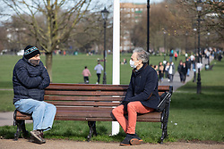 © Licensed to London News Pictures. 21/03/2020. LONDON, UK. Two men practice social distancing as they enjoy the sun on Clapham Common, London, on 21 March 2020. The government has recently asked people to practice social distancing in order to stop the spread of the Coronavirus. Photo credit: Luke Dray/LNP