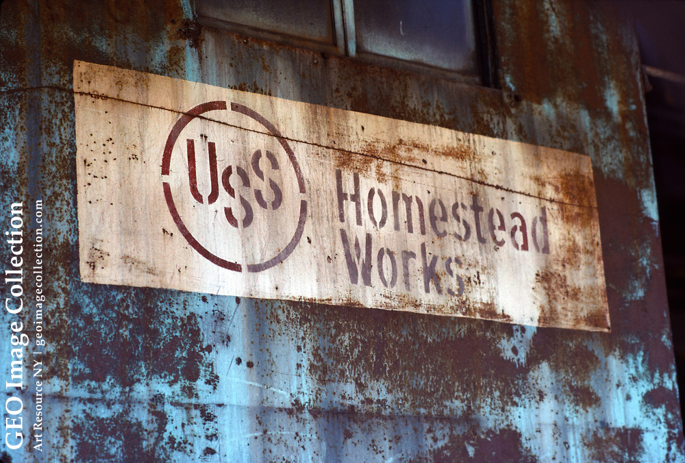 Faded and rusted sign and logo for USS Homestead Works, a steel mill of U.S. Steel near Pittsburgh. This was once the world's largest steel producing industrial plant. Started in 1901 and closed in 1986, the USX steel mill is typical of many obsolete rust belt industry sites that closed with decline of steel making in the Allegheny region. The plant was later demolished and the riverfront property redeveloped.