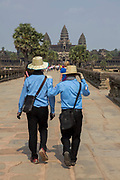 Two tour guides dressed in uniform walk along the stone walkway surrounding Ankor Wat temple complex in Krong Siem Reap, Cambodia. Angkor Wat is a temple complex in Cambodia and the largest religious monument in the world, with the site measuring 162.6 hectares. It is Cambodia's main tourist destination.