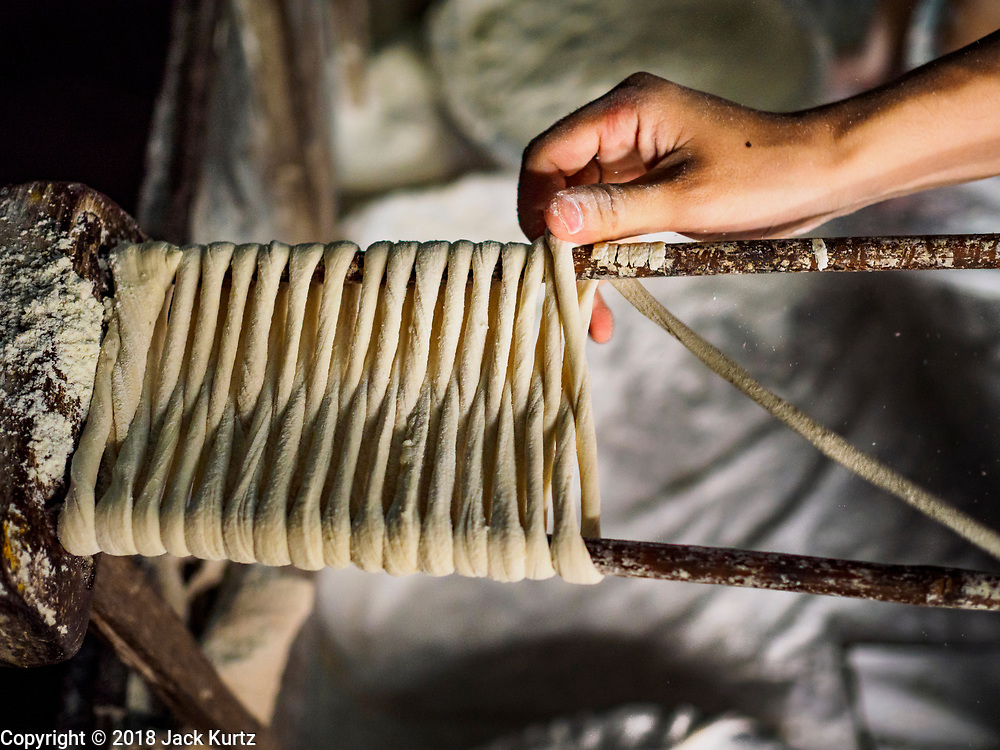 """29 DECEMBER 2018 - BANGKOK, THAILAND: Longevity noodles wrapped on wooden sticks before starting the drying process in a family shophouse. From here the noodles will go into a drying cabinet for two hours before being stretched and dried in the sun for three hours. The family has been making traditional """"mee sua"""" noodles, also called """"longevity noodles"""" for three generations in their home in central Bangkok. They use a recipe brought to Thailand from China. Longevity noodles are thought to contribute to a long and healthy life and  are served on special occasions, especially Chinese New Year, which is February 4, 2019. These noodles were being made for Chinese New Year.       PHOTO BY JACK KURTZ"""