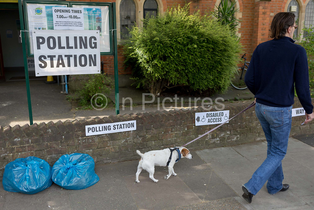 On the morning of the European Elections in the UK, a local man walks his dog past the Polling Station at the Baptist Church in East Dulwich. Barnabas Parish Hall in Dulwich Village, on 23rd May 2019, in south London, England UK.