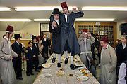 During the Jewish festival of Purim a group of Orthodox Jewish boys from the Viznitz Yeshiva (school) in fancy dress celebrate the festival with a feast. The evening quickly moves onto dancing on the tables that sends food flying everywhere. The school boys drink large amounts of alcohol throughout the day and night.