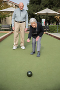 A senior women rolling a bocce ball with her friend