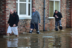 © Licensed to London News Pictures. 27/12/2015. York, UK.  People walk through floodwater with home made waterproof leggings in York City centre. Large areas of the North of England have been hit by severe flooding following unusually heavy rainfall in December. Photo credit: Ben Cawthra/LNP