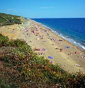 Crowded summer beach at Burton Mere near West Bay, Dorset, England, UK