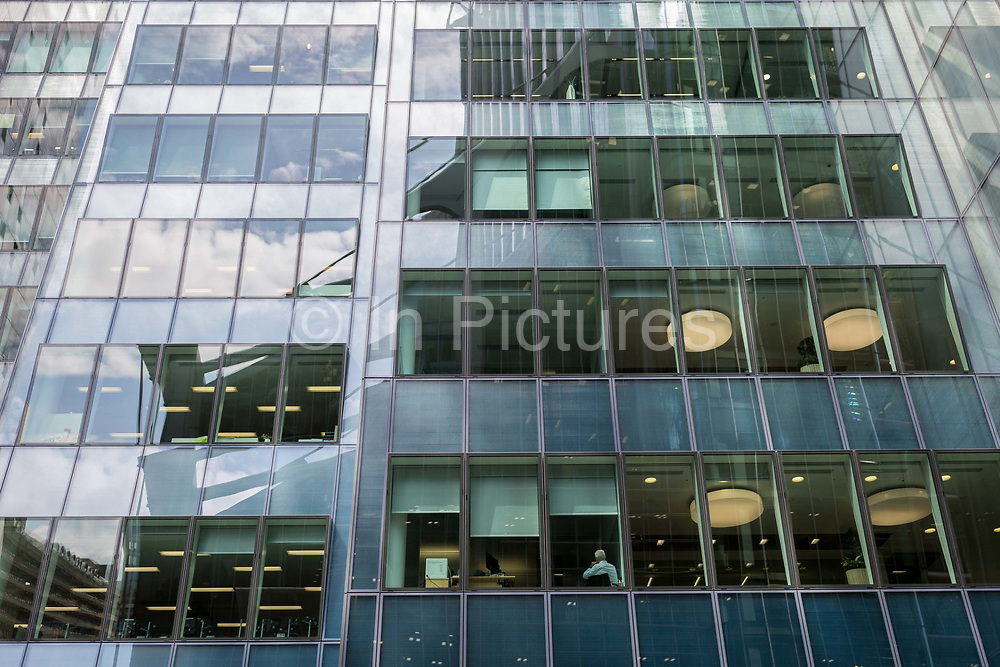A businessman sits with his back to the window on a lower floor of his corporate office building in the City of London, the capitals financial district - aka the Square Mile, on 8th August, in London, England.