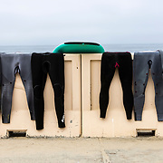 Wetsuits hang to dry along a wall in Malibu.