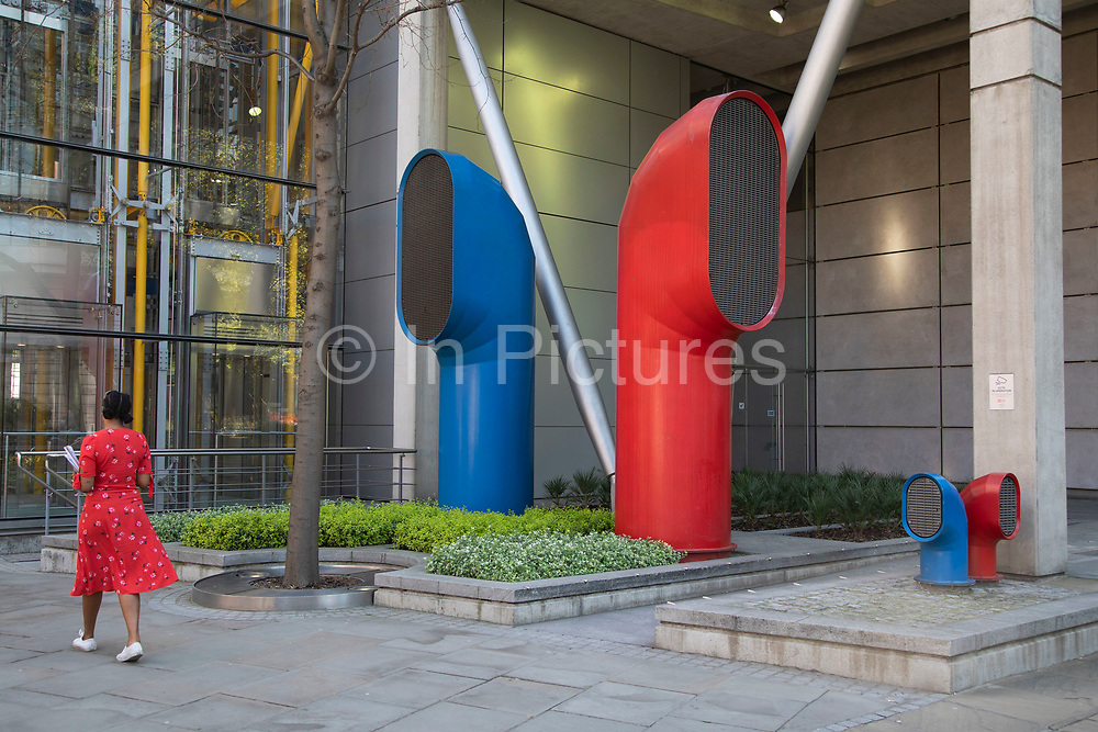 Woman wearing a red dress interacts with the red and blue air ducts shaped like funnels, which are part of Vents 88 on London Wall by architect Richard Rogers, appear as strange architectural elements in the City of London, England, United Kingdom. 88 Wood Street is a commercial office tower development in the City of London, England. The architects were Richard Rogers Partnership, now known as Rogers Stirk Harbour + Partners. The building was constructed between 1993 and 2001 and was known as one of the Roger's buildings which placed normally concealed internal elements (like ventilation ducts) on the outside of the building allowing more internal space.