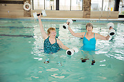 Senior women friends in pool doing water aerobics with weights