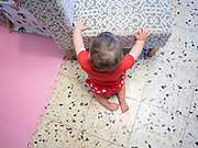 1 year old female baby in red clothes crawls on the floor