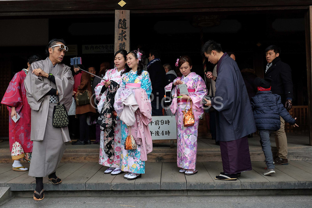 Tourists taking selfies while dressed in traditional Japanese kimonos. Kyoto, Japan