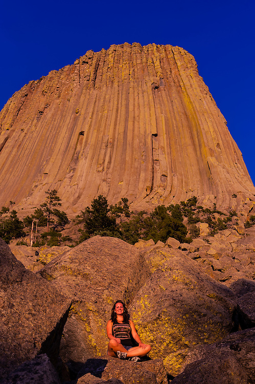 Teenaged girl in front of the 867 foot tall Devils Tower (a granite monolith which is a sacred site to American Indians), Devils Tower National Monument, Wyoming USA