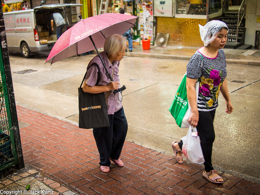 13 AUGUST 2013 - HONG KONG:  People near Gage Street in Hong Kong use umbrellas and plastic bags to protect themselves from the rains of Typhoon Utor. Typhoon Utor (known in the Philippines as Typhoon Labuyo) is an active tropical cyclone located over the South China Sea. The eleventh named storm and second typhoon of the 2013 typhoon season, Utor formed from a tropical depression on August 8. The depression was upgraded to Tropical Storm Utor the following day, and to typhoon intensity just a few hours afterwards. The Philippines, which bore the brunt of the storm, reported 1 dead in a mudslide and 23 fishermen missing at sea. The storm brushed by Hong Kong bringing several millimeters of rain and moderate winds to the island but causing no reported damage or injuries. It is expected to make landfall in China.  PHOTO BY JACK KURTZ