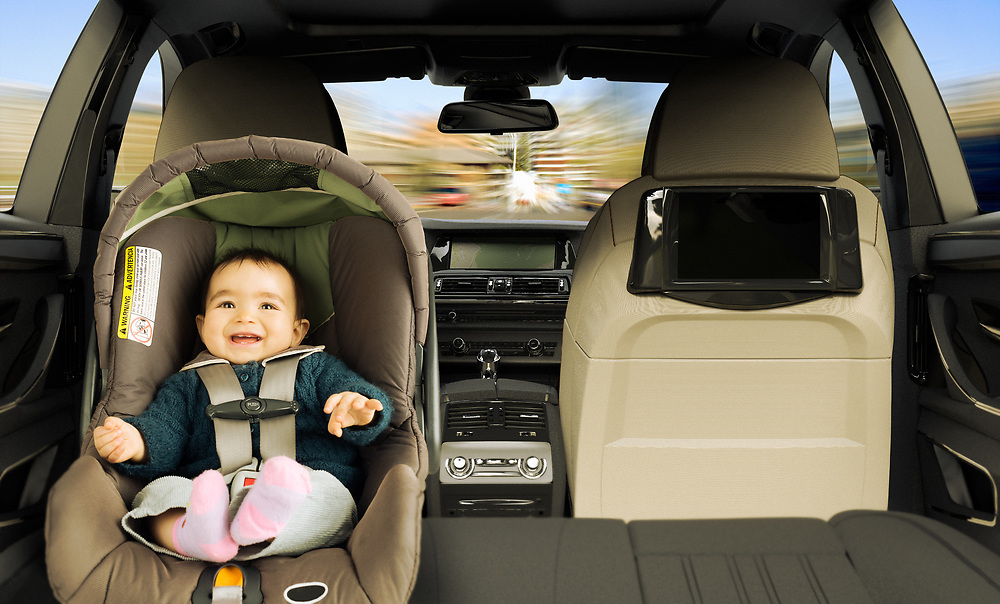 3D reendering of a baby girl in the back seat of a car in a child safety seat.