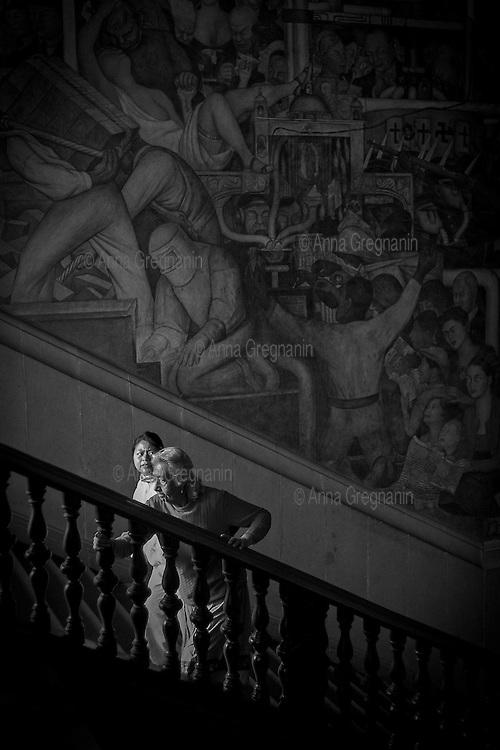 """città del Messico, due donne salgono le scale di Palazo Nazionale. Alle loro spalle il murale di Diego Rivera """"la lotta di classe"""""""