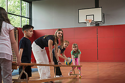 Teacher and students carrying bench in sports hall, Munich, Bavaria, Germany