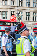 A member of XR walked over a government-owned vehicle after Police intervened rapidly as Members of Extinction Rebellion (XR) drove a truck right outside the main entrance of Westminster Palace, Houses of Parliament in central London. XR activists had loaded a pink boat 'TELL THE TRUTH' in the truck. Dozens of XR members had chained themselves on the boat already. Thursday, Sept 10, 2020 - marks final 10th day of rebellion in London. Environmental nonviolent activists group Extinction Rebellion enters its 10th and final day of continuous ten days protests to disrupt political institutions throughout peaceful actions swarming central London into a standoff, demanding that central government obeys and delivers Climate Emergency bill. (VXP Photo/ Vudi Xhymshiti)