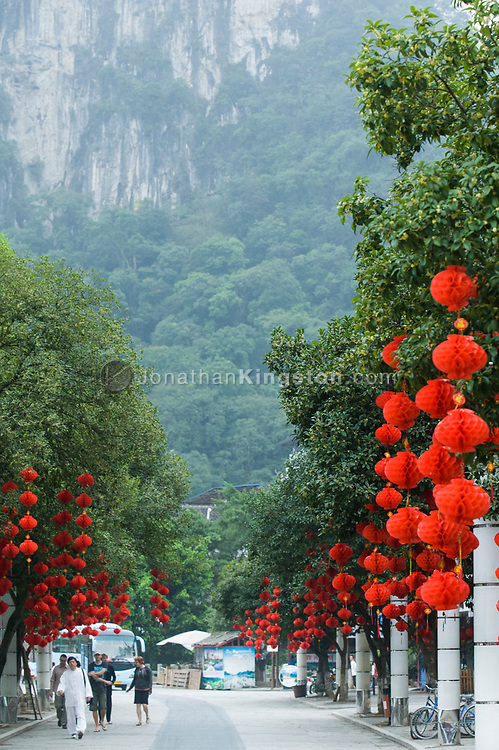 Red decorative paper globes hang from trees in celebration of Chinese National Day along a street in Yangshuo, China.