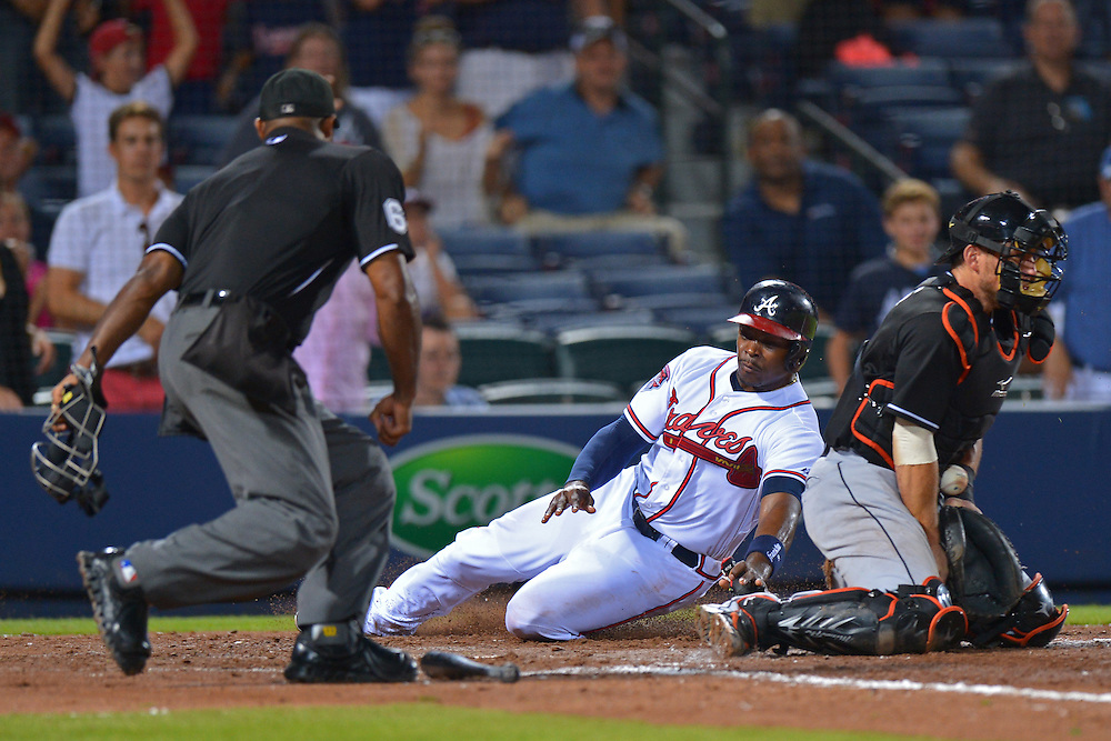 Jul 22, 2014; Atlanta, GA, USA; Atlanta Braves left fielder Justin Upton (8) scores as Miami Marlins catcher Jeff Mathis (6) fields the ball during the eighth inning at Turner Field. Mandatory Credit: Kevin Liles-USA TODAY Sports