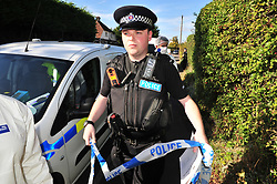 © Licensed to London News Pictures. 29/09/2018<br /> HADLOW, UK.<br /> Police officer with tape.<br /> A murder investigation has been launched in Hadlow,Kent after the deaths of two women at Carpenters Lane. A 28 year old man has been arrested on suspicion of murder after three people suffered serious injuries. Police forensic officers are at the scene inside two properties 26 and 24 Carpenters Lane.<br /> Photo credit: Grant Falvey/LNP