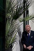 A businessman checks his messages beneath the shadows of a potted plant outside an Itsu shop in the Square Mile, on 3rd March 2017, in the City of London, England.